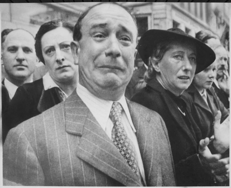 A French man weeps as German soldiers march into Paris on June 14, 1940, after the Allied armies had been driven back across France..jpg