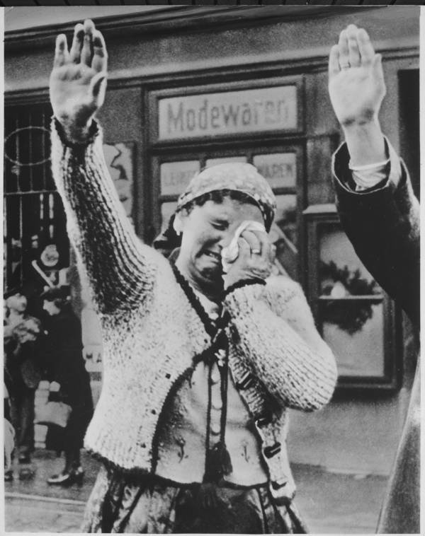 A Sudeten woman from the area that is now the Czech Republic salutes the conquering German forces while crying at the fall of her people to the Nazis, circa 1942-1945..jpg