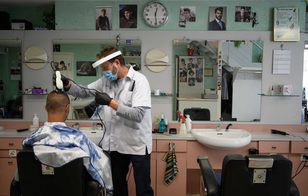 A barber wears protective equipment as he cuts a customers hair in Lausanne, Switzerland, on April 27.Fabrice Coffrini-AFP-Getty Images.jpg
