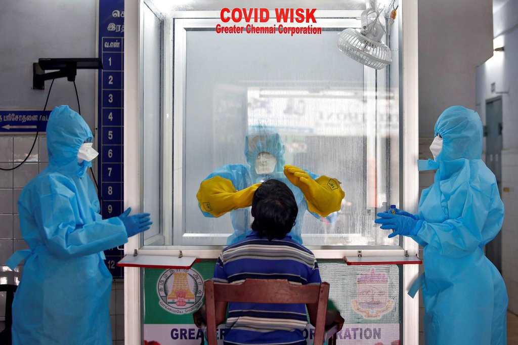 A doctor in a protective chamber tests a patient for coronavirus at a walk-in kiosk in Chennai, India, on April 13.P. Ravikumar-Reuters.jpg
