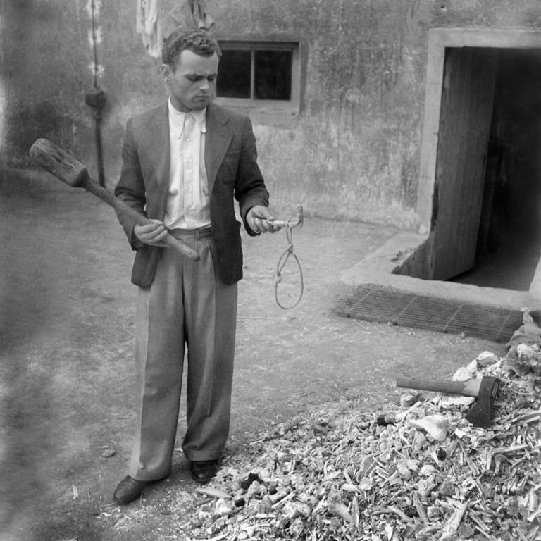 A man holds a noose used for hanging prisoners at the Buchenwald concentration camp following its liberation by U.S. forces in April 1945..jpg