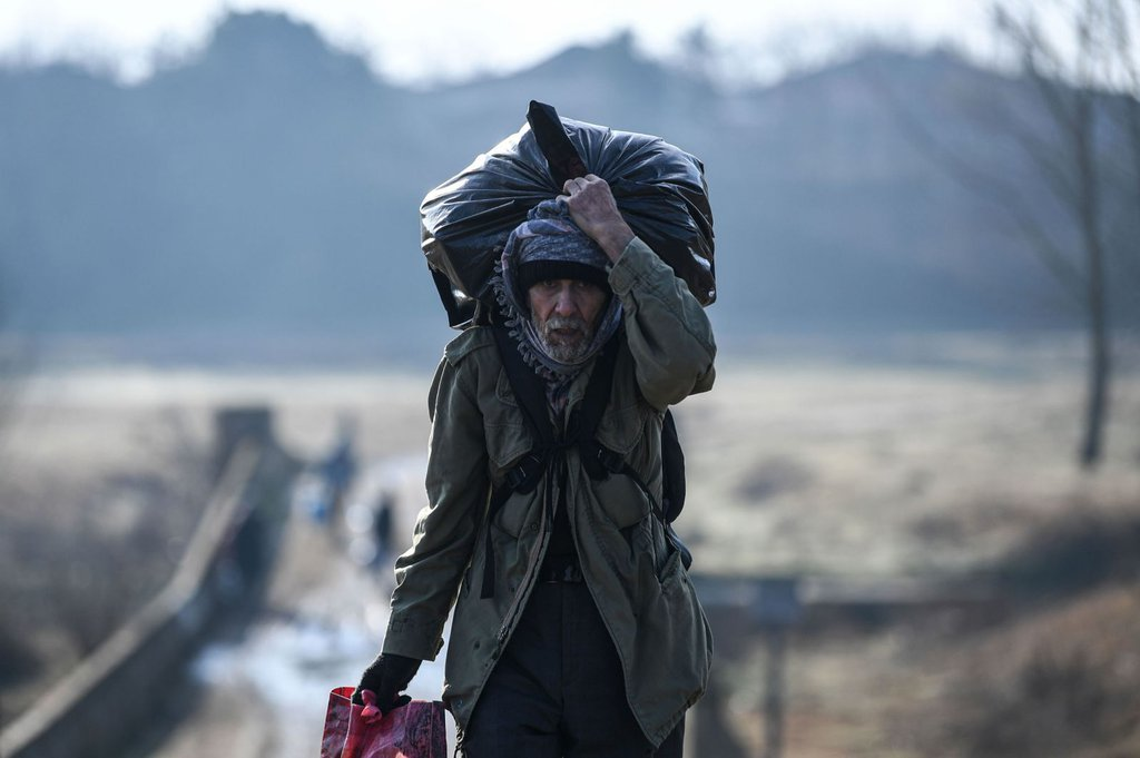 A migrant carries his belongings as he walks toward the Maritsa river to attempt to cross to the Greek side.Ozan Kose AFP.jpg
