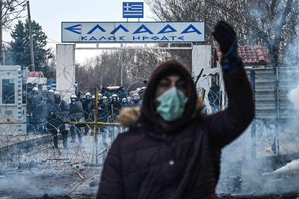 A migrant gestures as Greek police officers use tear gas at the Pazarkule crossing on February 29.Ozan KoseAFP.jpg