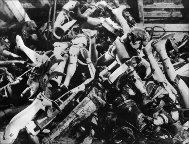 A pile of prostheses belonging to the murdered victims of the Auschwitz concentration camp in Poland following its liberation, January 1945..jpg