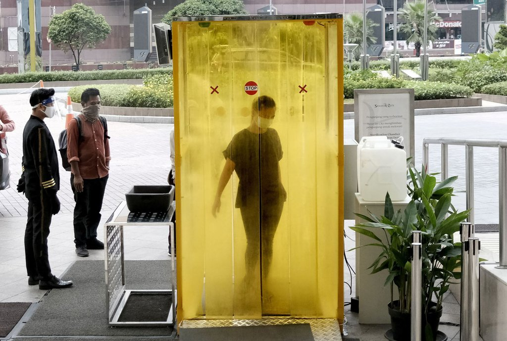 A woman is sprayed with disinfectant before entering a shopping mall in Jakarta, Indonesia, on June 9.Dita Alangkara-AP.jpg