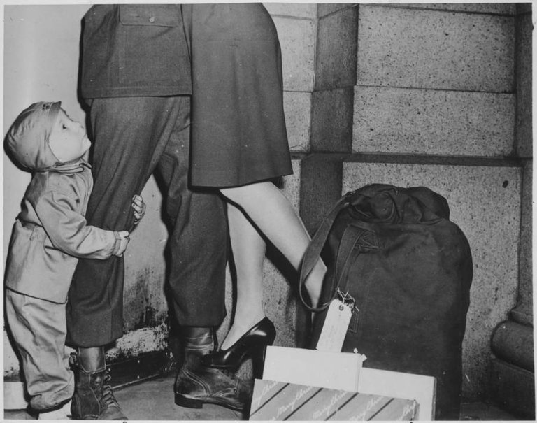 A young boy greets his father, a soldier allowed to return home for Christmas, 1944..jpg