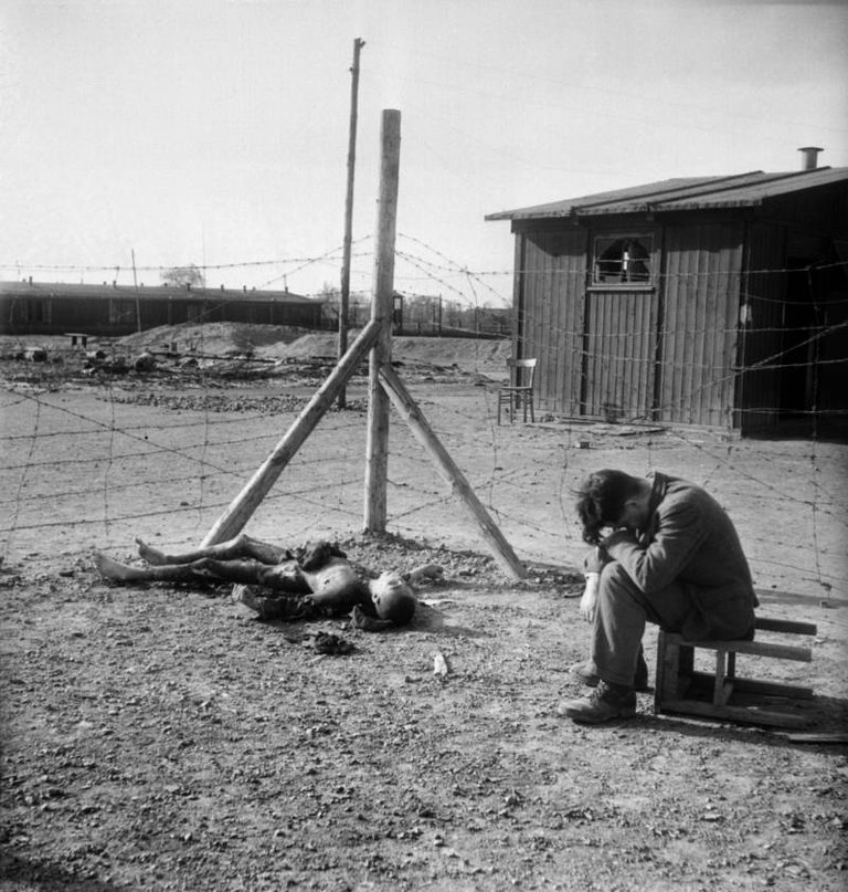 A young man sits on an overturned stool next to a burnt body inside the Thekla concentration subcamp outside Leipzig, Germany soon after its liberation by U.S. forces on April 18, 1945..jpg