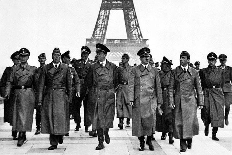 Adolf Hitler and his entourage walk near the Eiffel Tower in Paris on June 23, 1940, following the occupation of France by the Nazis..jpg