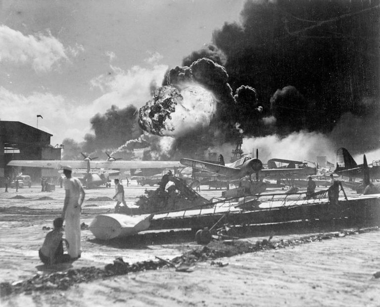 American sailors stand amid wrecked planes at the Ford Island seaplane base, watching as the USS Shaw explodes in the center background during the Japanese raid on Pearl Harbor, Hawaii on December 7, 1941..jpg