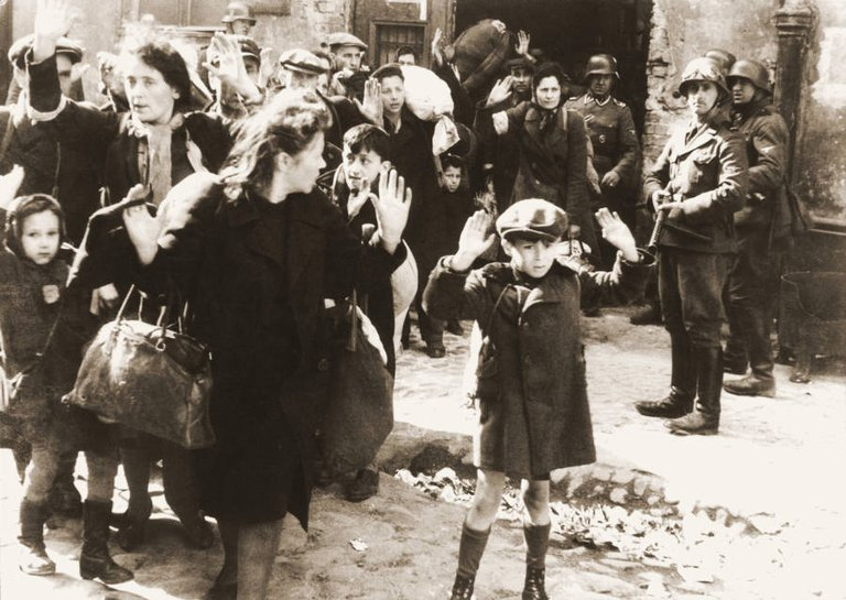 An unidentified boy raises his arms as German soldiers capture Polish Jews during the Warsaw ghetto uprising sometime between April 19 and May 16, 1943..jpg