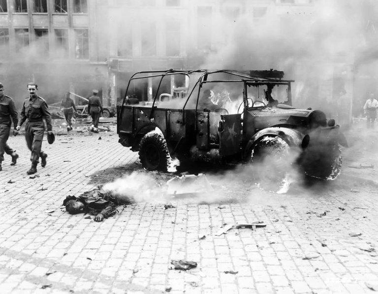 Bystanders look on as a boy's burning corpse lies next to the jeep he was in, which was struck by a German V-2 rocket in Antwerp, Belgium on November 27, 1944..jpg