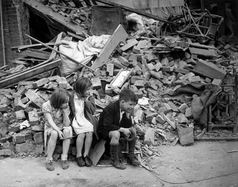 Children of an eastern suburb of London, who have been made homeless by German bombings, sit outside the wreckage of what was their home, September 1940..jpg