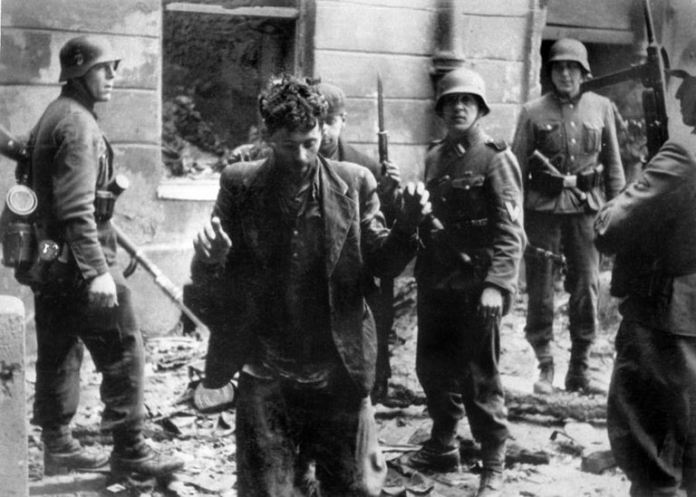 German soldiers arrest a Jewish man in Warsaw, Poland following the ghetto uprising that had recently occurred there, April 1943..jpg