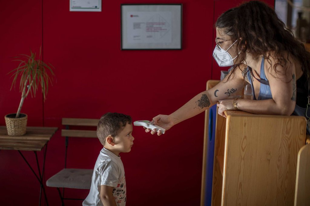 Hugo, 3, has his temperature taken by a teacher as he arrives at kindergarten in Barcelona on June 26.Emilio Morenatti-AP.jpg