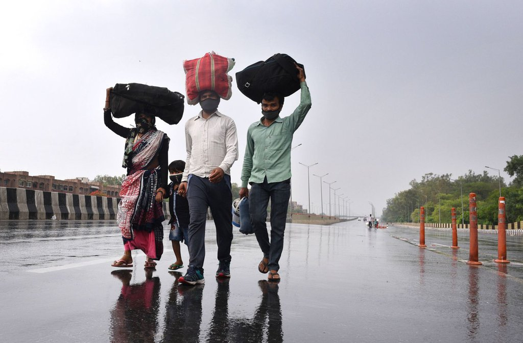 Migrant workers in New Delhi walk toward the Sarai Kale Khan Bus Terminus on May 3 after learning that the government was preparing to send migrant workers back to their home states during the lockdown..jpg