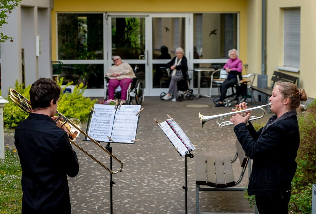 Musicians play their instruments for a retirement home in Karben, Germany, on April 13.Michael Probst-AP.jpg