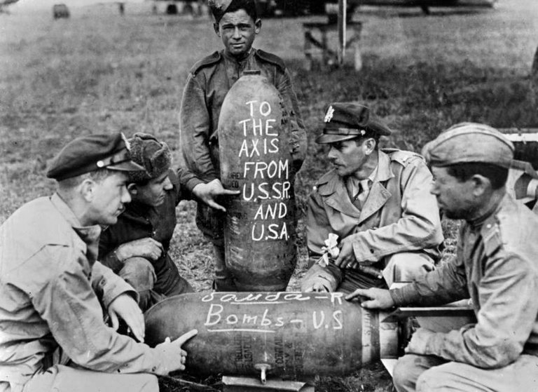 Soviet and American airmen pose with the bombs on which they'd written messages for the Nazis at a Russian air base on June 2, 1944..jpg