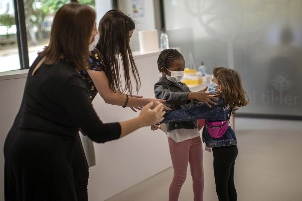 Teachers in Barcelona, Spain, try to prevent a hug between 6-year-olds Wendy Otin and Oumou Salam Niang as they meet on the first day of school following a lockdown.Emilio Morenatti-AP.jpg