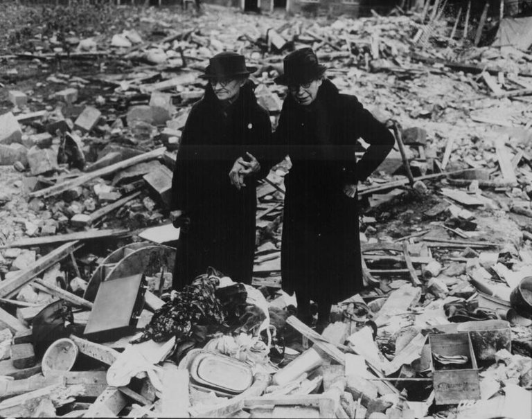 Two women stand amid the leveled ruins of the almshouse that was their home before a German bombing raid destroyed it in Newbury, England on February 11, 1943..jpg